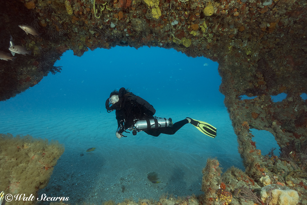 At a depth of 24m (80 ft), a rebreather diver passes a large hole in the port side of the Mizpah's aft haul section.
